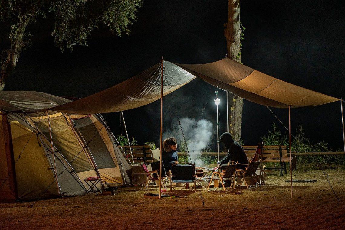 deux personnes attablées devant une tente de camping